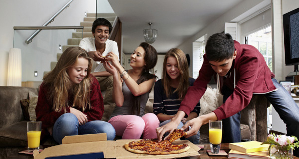 Teenagers having take away pizza
